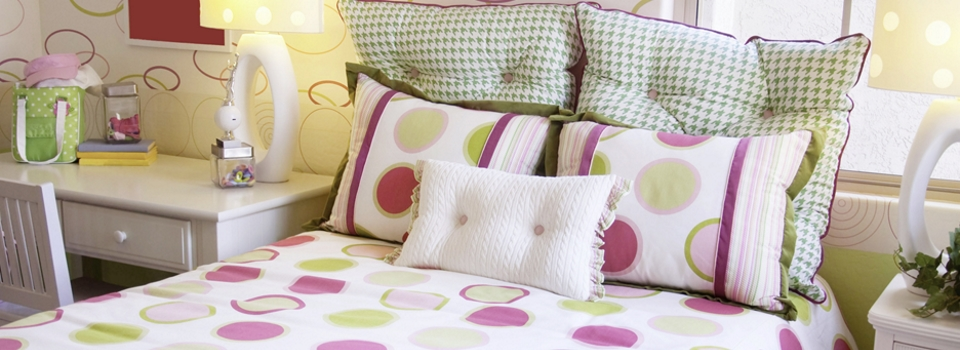 bed with bedding in bright colours on white background